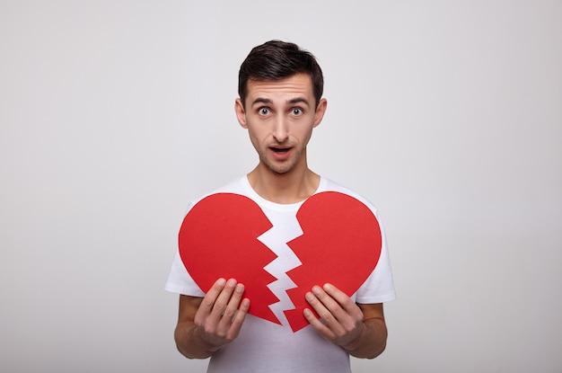 Verraste knappe kerel met een rood gebroken hart in zijn handen.