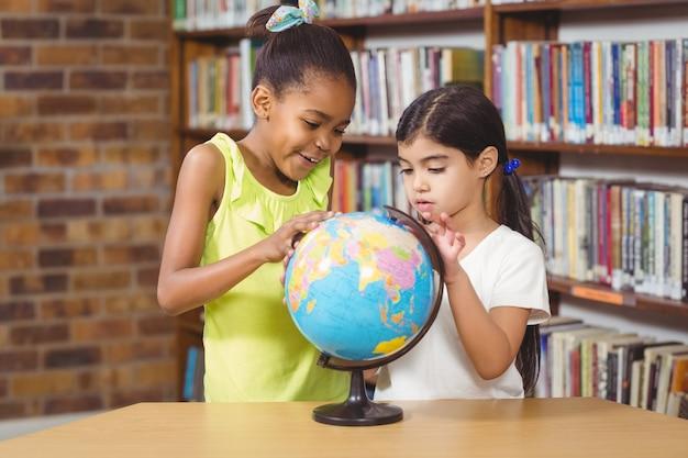Verraste leerlingen die globe in de bibliotheek bestuderen