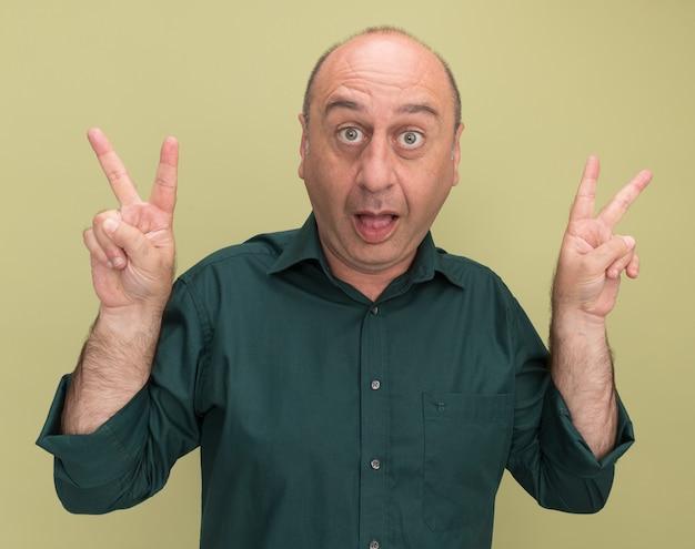 Verraste man van middelbare leeftijd die groen t-shirt draagt dat vredesgebaar toont dat op olijfgroene muur wordt geïsoleerd