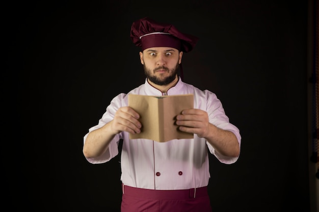 Verraste mannelijke kok die in schort op receptenboek kijken op zwarte