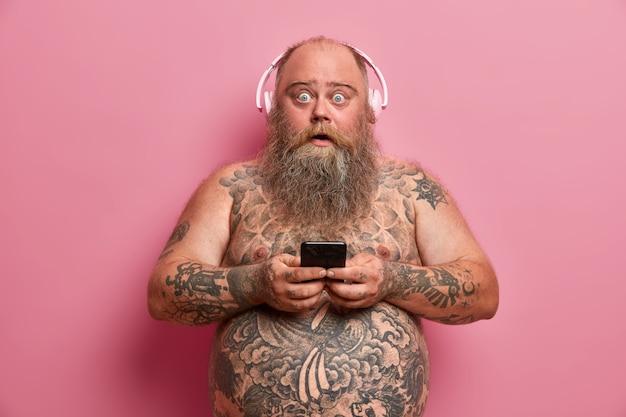 Verraste mollige man staart en zegt wow, sms't met vriend via smartphone, draagt koptelefoon op oren, luistert naar muziek, poseert shirtless, heeft een getatoeëerd lichaam. technologie en vrijetijdsconcept