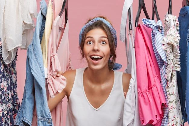 Verraste mooie vrouw die met wijd geopende mond en ogen kijkt terwijl ze in de buurt van een rek met kleren in haar kamer staat, geschokt door zo'n verscheidenheid aan jurken en blouses. lichaamstaal concept