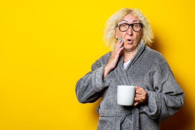 Verraste oude vrouw die met glazen en grijze badjas een kop houdt