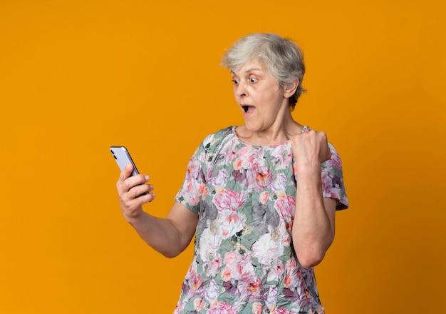 Verraste oudere vrouw die vuist opheft die telefoon bekijkt die op oranje muur wordt geïsoleerd