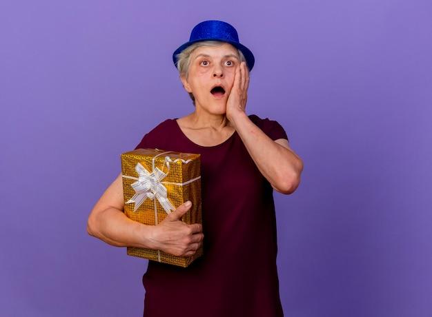 Verraste oudere vrouw met feestmuts legt hand op gezicht met geschenkdoos geïsoleerd op paarse muur met kopie ruimte