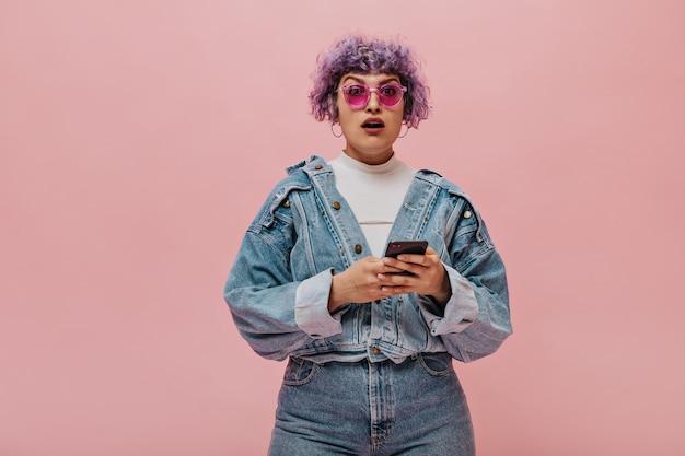 Verraste paarsharige vrouw in roze glazen en denimkostuum. vrouw met grote ronde oorbellen houdt telefoon vast.