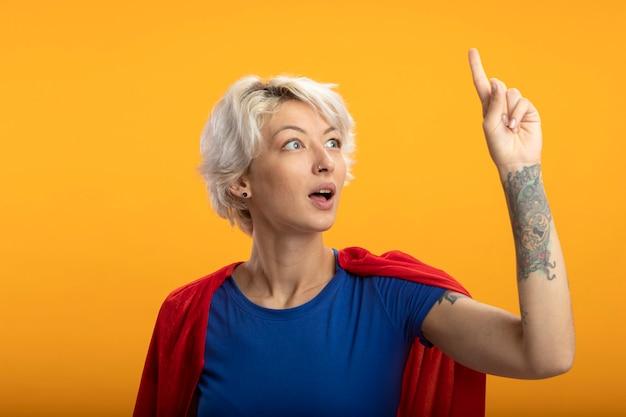 Verraste supervrouw met rode cape wijst omhoog geïsoleerd op oranje muur