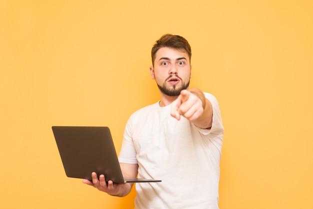 Verraste tiener in een wit t-shirt staat op geel met een laptop in zijn handen