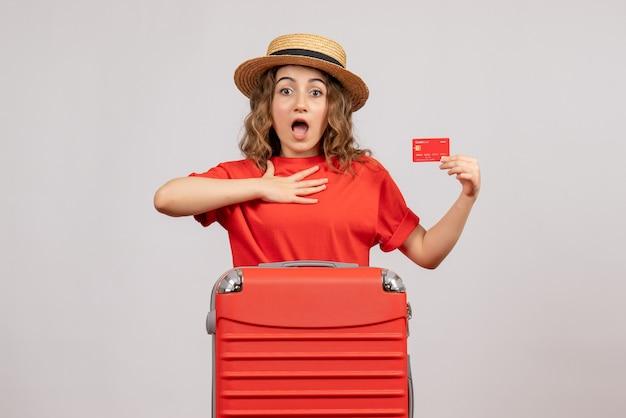 Verraste vakantievrouw met haar valise holding card