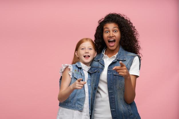 Verraste vrolijke jonge dames in vrijetijdskleding met grote ogen en mond open, vooruit wijzend met opgeheven wijsvinger terwijl ze poseren op roze