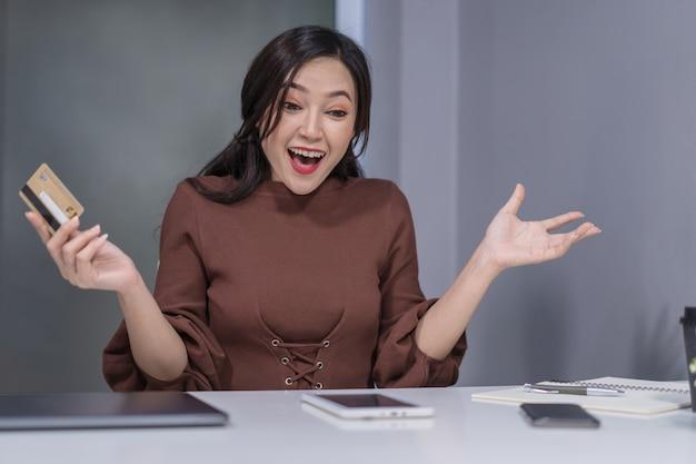 Verraste vrouw die digitale tablet voor online het winkelen met creditcard gebruiken