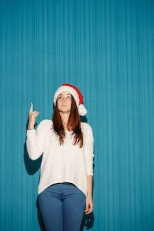 Verraste vrouw die een kerstmuts draagt die op blauwe studioachtergrond wijst