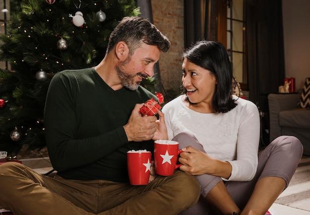 Verraste vrouw die haar echtgenoot met een gift bekijkt