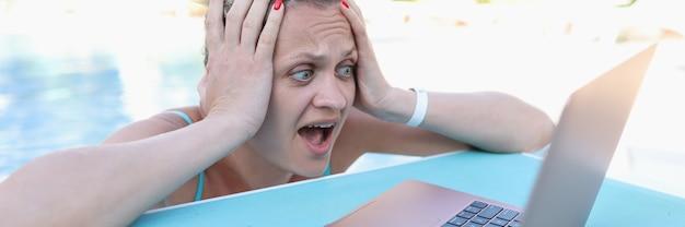 Verraste vrouw die haar hoofd vasthoudt en naar het scherm van de laptop aan de zijkant van het zwembad kijkt