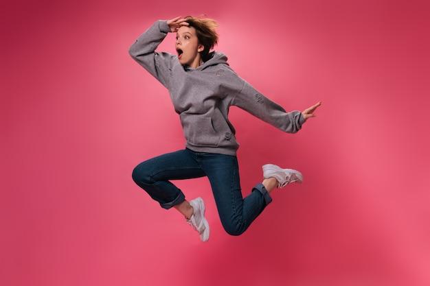 Verraste vrouw die in grijze hoodie op roze achtergrond springt. geschokt kortharig meisje in spijkerbroek beweegt en danst op geïsoleerde achtergrond