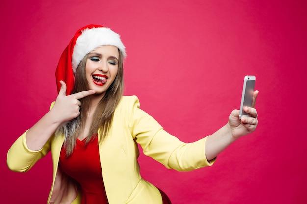 Verraste vrouw die in santahoed selfie over roze achtergrond maakt.