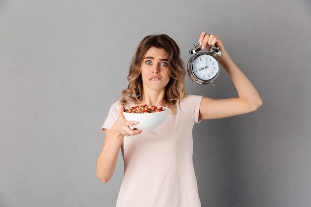 Verraste vrouw die in t-shirt gezond voedsel in plaat en wekker houden terwijl haar lip en over grijs bijt