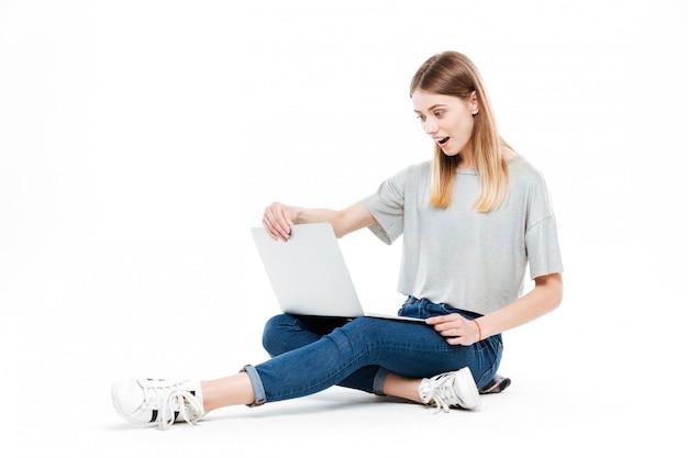 Verraste vrouw die laptop computer met behulp van