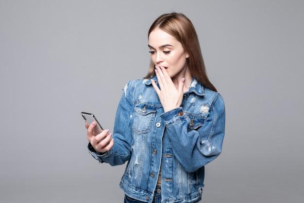 Verraste vrouw die mond behandelt, die het scherm van de mobiele telefoon bekijkt, geschokt vrouw die onverwacht bericht leest, het winkelen aanbieding, goed nieuws, die cellphone houdt, die op grijze muur wordt geïsoleerd