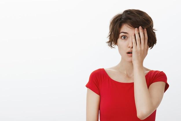 Verraste vrouw die naar adem snakt en verbaasd kijkt, bedekt de helft van het gezicht
