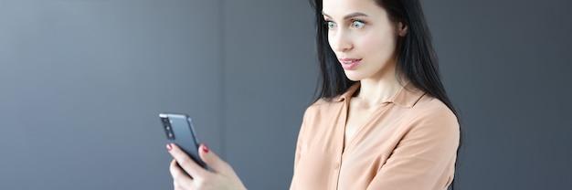 Verraste vrouw die naar het scherm van de mobiele telefoon kijkt