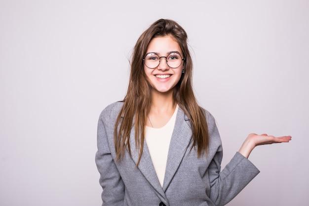 Verraste vrouw die open handpalm met exemplaarruimte toont voor product of tekst op witte achtergrond