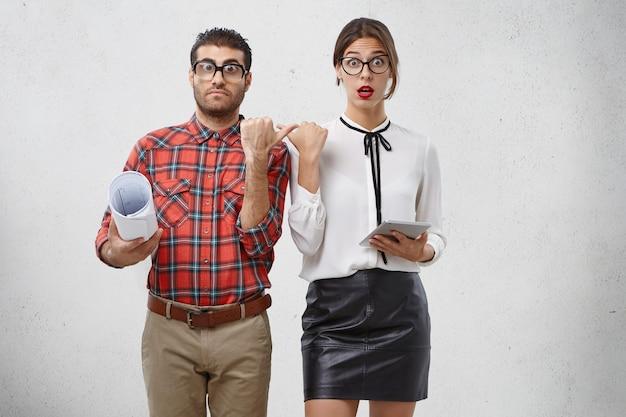 Verraste vrouw en man wijzen naar elkaar, hebben een verbaasde uitdrukking,