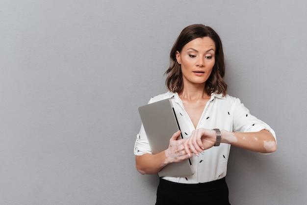 Verraste vrouw in bedrijfskleren met laptop in hand kijkend op polshorloge op grijs