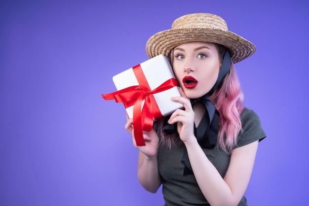 Verraste vrouw in een strohoed die het geschenk in haar handen toont