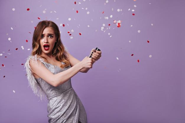 Verraste vrouw in glanzende outfit die confetti op paarse muur gooit
