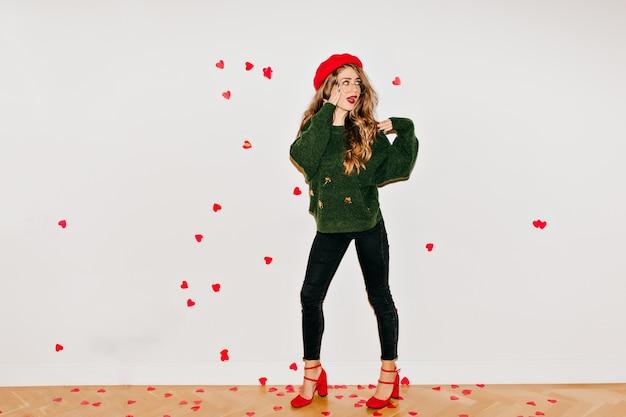 Verraste vrouw in rode sandalen en baret die zich onder hartconfettien bevindt