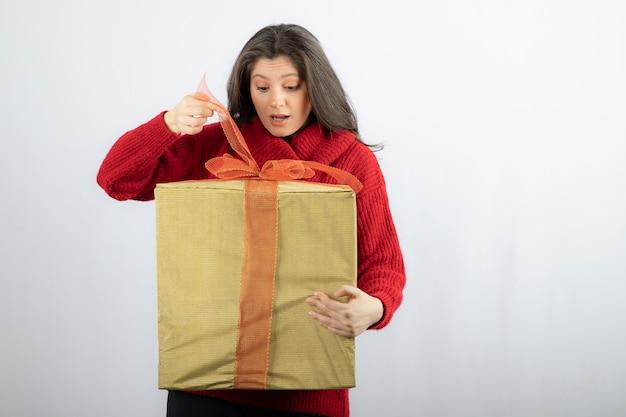 Verraste vrouw in rode trui die een doos met kerstcadeau opent.