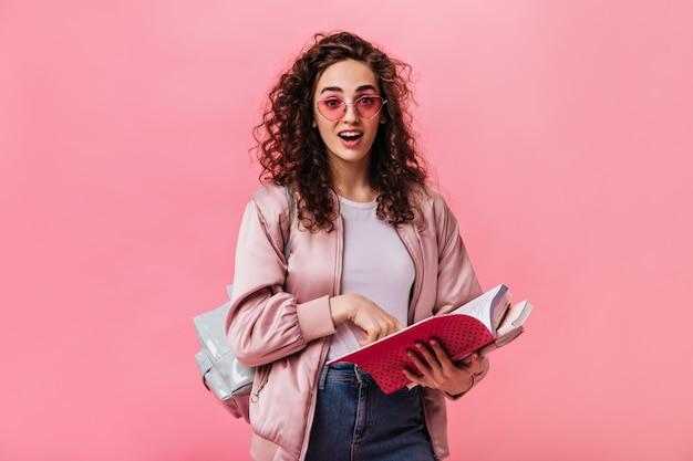 Verraste vrouw in roze jasje en spijkerbroek poseren met boeken over geïsoleerde achtergrond