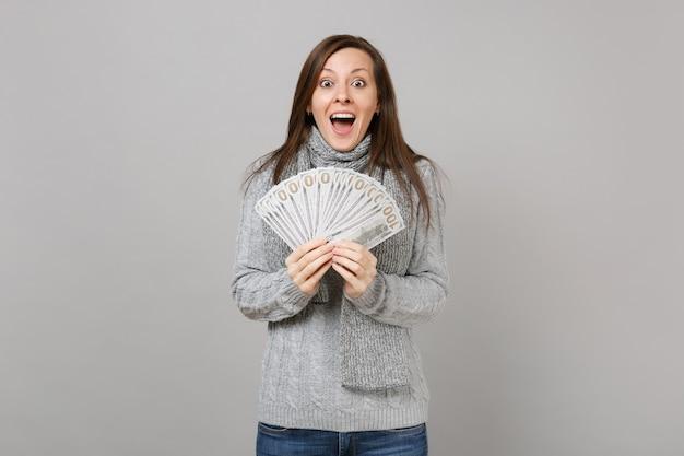 Verraste vrouw in trui, sjaal die mond wijd open houdt, veel dollarsbankbiljetten vasthoudt, contant geld geïsoleerd op een grijze achtergrond. gezonde mode levensstijl mensen emoties, koude seizoen concept.