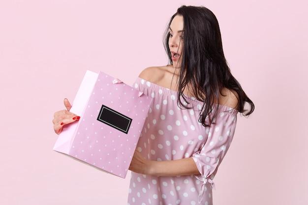 Verraste vrouw kijkt in cadeauzakje, draagt een jurk met stippen, heeft lang zwart haar, poseert op lichtroze, vraagt zich af of ze een duur cadeau ontvangt, is geschokt. mensen en verbazing concept