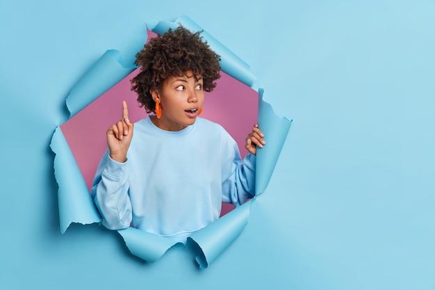 Verraste vrouw kijkt met grote belangstelling opzij wijsvinger opheffen adem inhouden van verbazing draagt basic trui breekt door papieren muur roept noodzakelijke informatie op