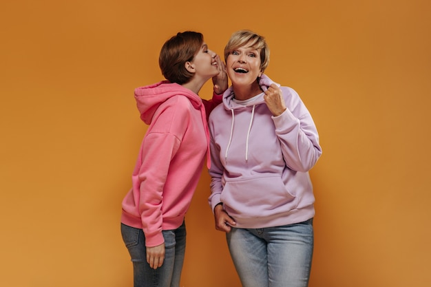 Verraste vrouw met blond haar in lila sweatshirt en spijkerbroek luisteren naar geheim van kleindochter op oranje achtergrond.