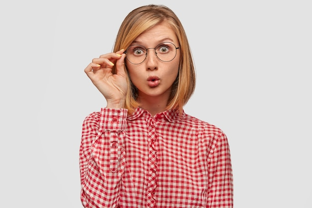 Verraste vrouw met europees uiterlijk die stomverbaasd is door plotseling nieuws in de wereld, staart door een bril