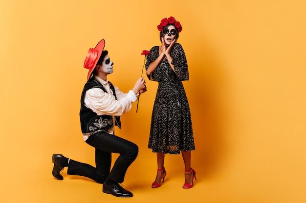 Verraste vrouw met schedelmasker in vreugdevolle schok, terwijl haar vriend in mexicaanse kleren knielend haar rode bloem geeft.