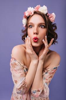 Verraste vrouw met stijlvolle make-up en manicure poseren. binnen phofo van verbaasd meisje in circlet van geïsoleerde bloemen.