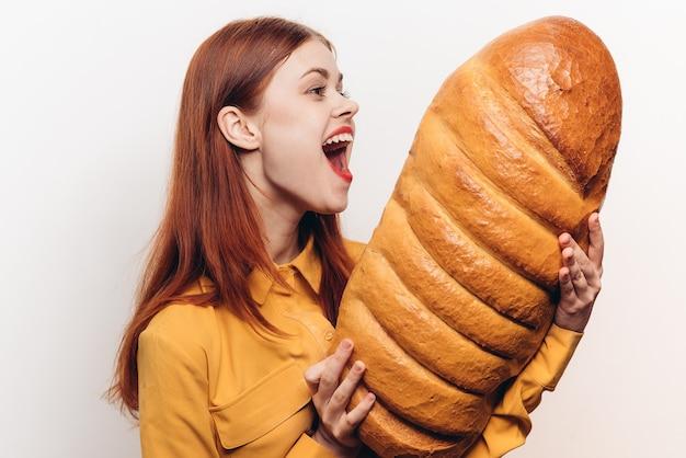 Verraste vrouw onderzoekt een brood in haar handen op een lichte muur.