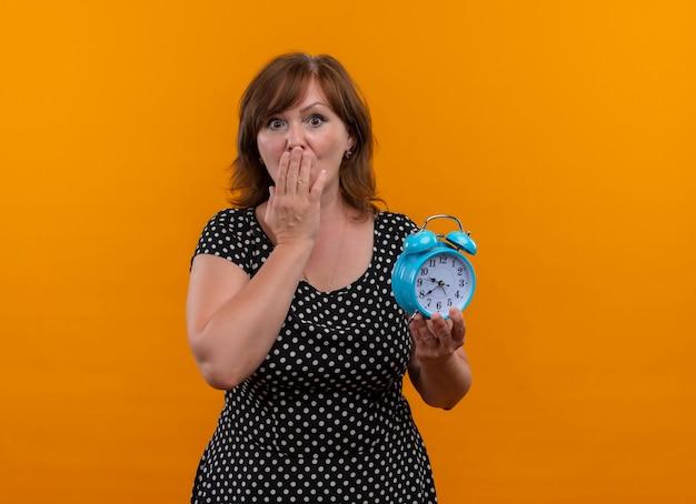 Verraste vrouw van middelbare leeftijd met wekker en hand op mond op geïsoleerde oranje muur met kopie ruimte