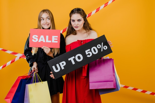 Verraste vrouwen hebben een uitverkoop tot 50% bord met kleurrijke boodschappentassen en signaalband geïsoleerd over geel