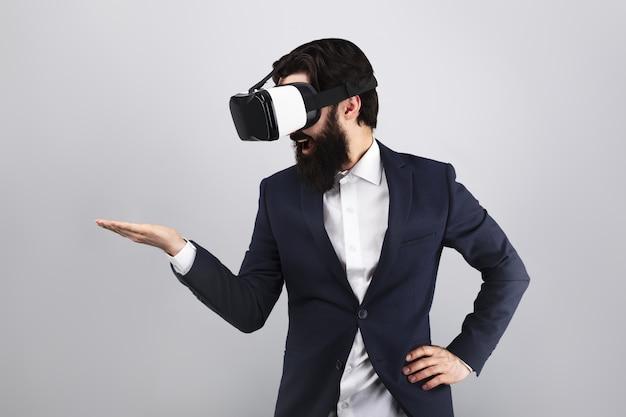 Verraste zakenman die in vr-bril op lege hand, virtual reality-concept, modelbeeld kijkt