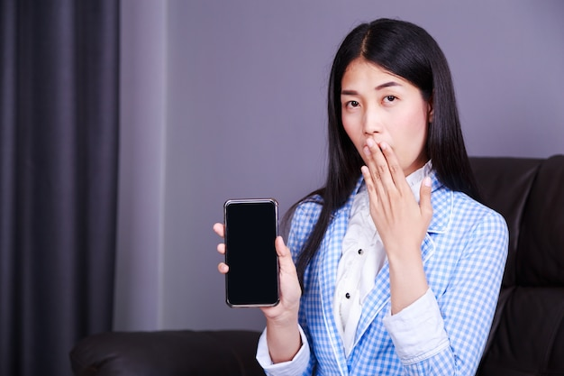 Verraste zakenvrouw met het tonen van de mobiele telefoon