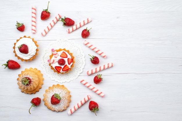 Verre bovenaanzicht van kleine cake met room en gesneden aardbeien snoepjes op wit bureau, fruitcake bessen zoete suiker bakken