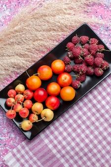 Verre bovenaanzicht van vers fruit, frambozen en pruimen in zwarte vorm op roze oppervlak