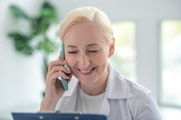 Verre overleg. blonde arts lacht en praat met de patiënt