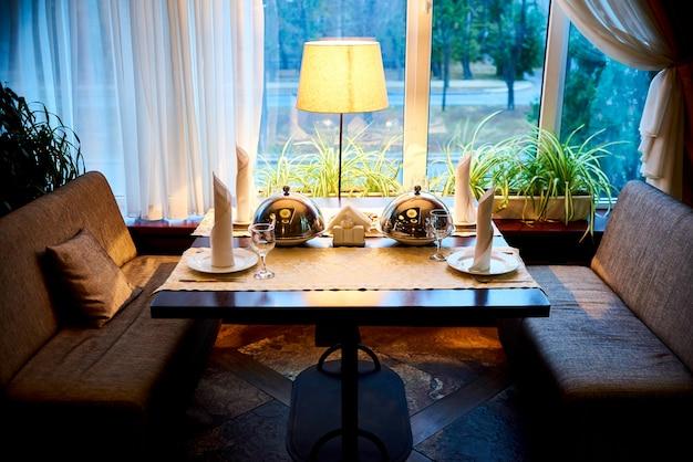 Verrekening tafel met een warme schotel onder de cloche bij het raam in het restaurant.