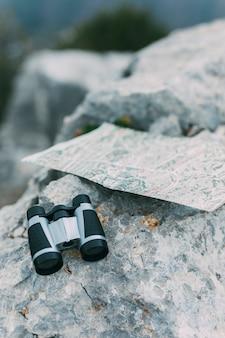 Verrekijker en kaart op rots